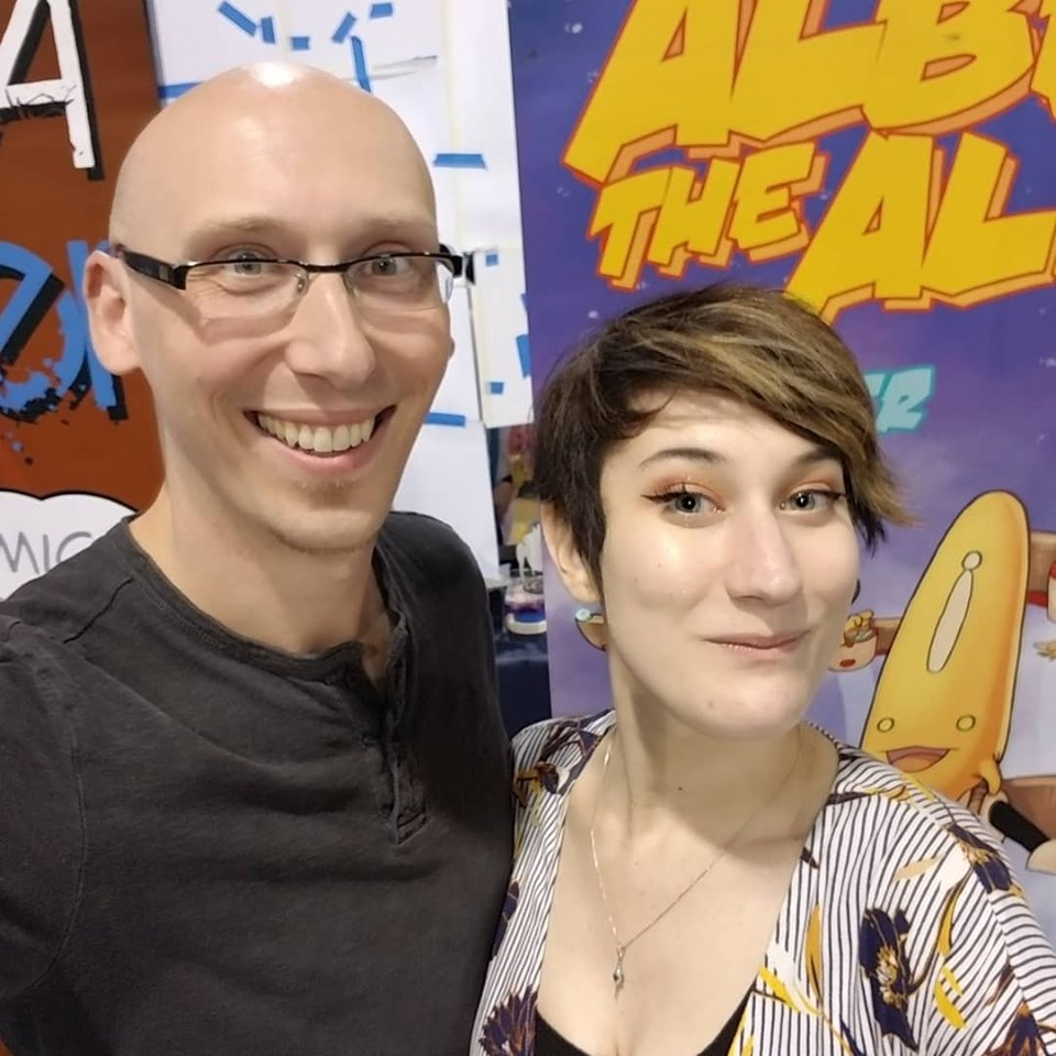 Comic writer and convention guest Trevor Mueller and volunteer Nikita Rauba at Anime Midwest 2019 albert the alien banner